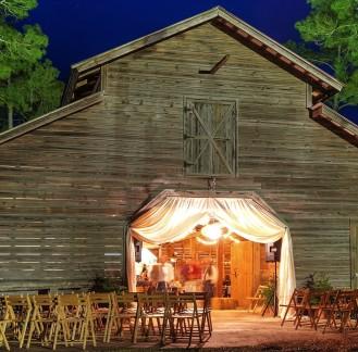 Wedding reception in lit up barn at night